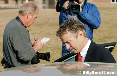 Associated Press photojournalist Ed Reinke (left) scribbles notes as Kentucky Senate candidate Rand Paul gets into a car after voting at Briarwood Elementary School on Tuesday, Nov. 2, 2010 in Bowling Green, Ky.