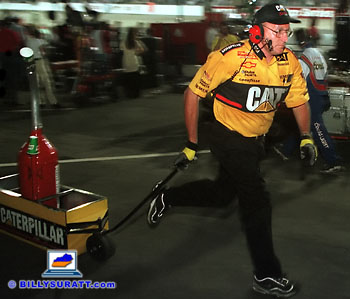 A Caterpillar team member rushes down pit row with a can of gas. Panning the camera combined with a slow shutter speed and rear curtain flash sync helps convey movement and a sense of urgency. (Copyright 1998 Billy Suratt)